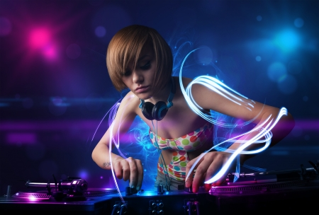 Beautiful disc jockey playing music with electro light effects and lights photo
