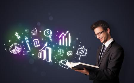 inteligencia: Chico joven que lee un libro con los iconos de negocios que sale del libro Foto de archivo