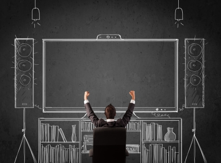 Young businessman sitting and enjoying home cinema system sketched on a chalkboard photo