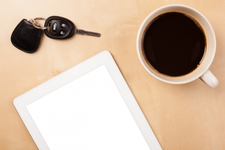 Tablet pc with copy space and a cup of coffee on a wooden work table close-up photo
