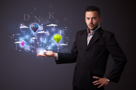 Young businessman holding shining letters and balloons in his hand photo