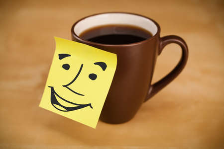 Drawn smiley face on a post-it note sticked on a cup photo