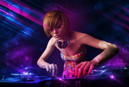 Beautiful young Dj playing on turntables with color effects photo