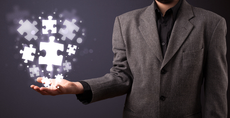 Businessman holding shining puzzle pieces in his hand Stock Photo - 24252683