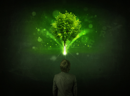 Young businessman standing with a glowing tree and letters above his head photo