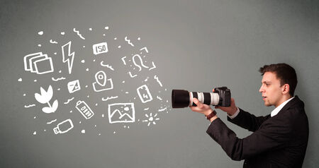 capturing: Young photographer boy capturing white photography icons and symbols Stock Photo