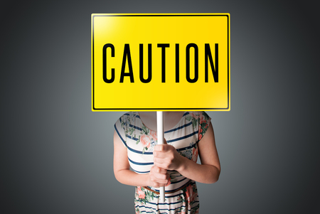 Young lady standing and holding a yellow caution sign in front of her head Stock Photo