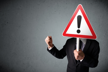Businessman holding a red traffic triangle warning sign in front of his head photo