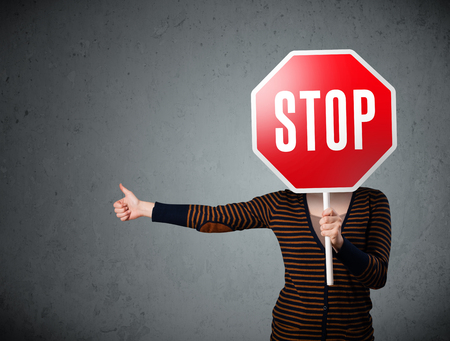 Young lady standing and holding a stop sign in front of her head photo