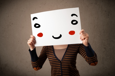 Young woman holding a cardboard with a smiley face on it in front of her head photo