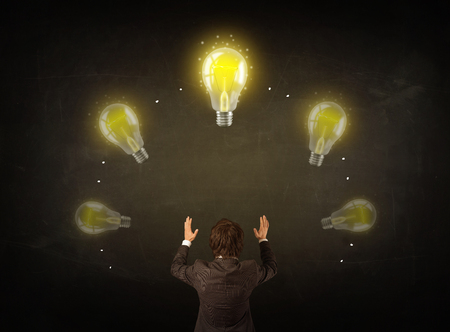 Young businessman thinking in front of a blackboard with glowing lightbulbs over his head photo