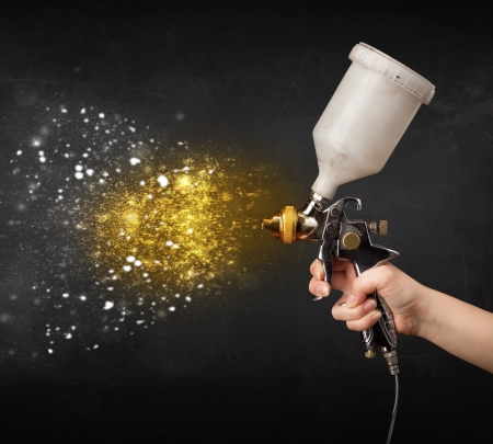 Worker with airbrush painting with glowing golden paint and particles photo