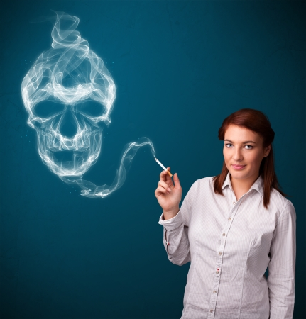 Pretty young woman smoking dangerous cigarette with toxic skull smoke Stock Photo - 24280823