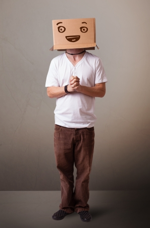 masquerader: Young man standing and gesturing with a cardboard box on his head with smiley face