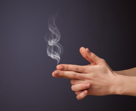 sense of security: Gun shaped man hand with smoke Stock Photo