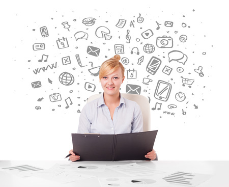 Beautiful young businesswoman with all kind of hand-drawn media icons  photo