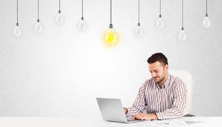 id�e lumineuse: L'homme d'affaires assis � table avec des ampoules id�e lumineuse Banque d'images