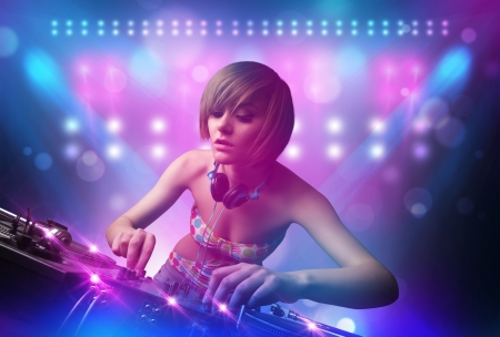 females: Pretty young disc jockey mixing music on turntables on stage with lights and stroboscopes Stock Photo