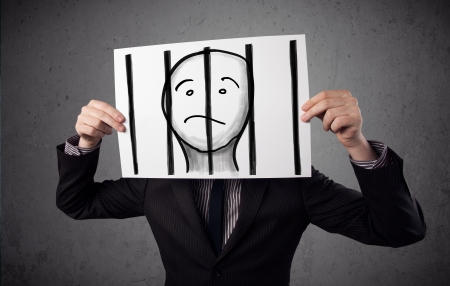 Businessman holding a paper with a prisoner in jail behind the bars on it in front of his head photo