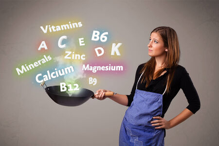 Pretty young woman cooking vitamins and minerals photo