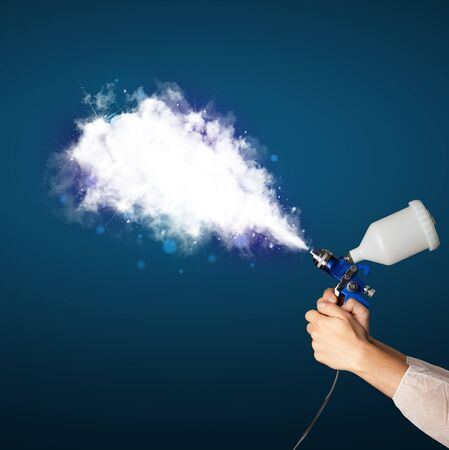 Painter with airbrush gun and white magical smoke concept photo