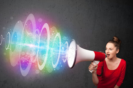 Cute young girl yells into a loudspeaker and colorful energy beam photo