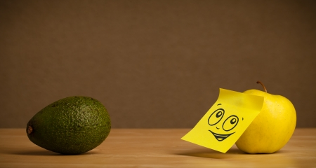 reacting: Apple with sticky post-it note reacting to avocado Stock Photo