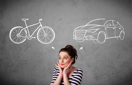 Pretty young woman taking a decision between bicycle and car photo