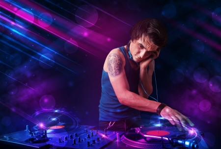 Attractive young DJ playing on turntables with color light effects photo