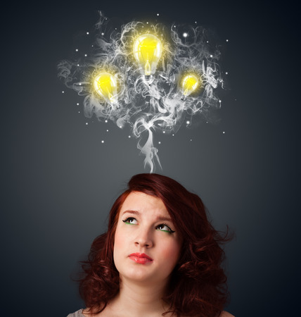 Pretty young woman with smoke and lightbulbs above her head photo