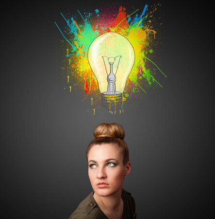 Pretty young woman gesturing with lightbulb and paint splashes above her head photo