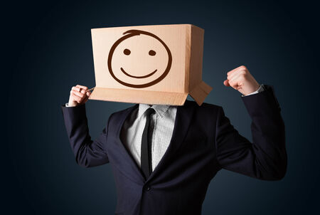 hiding face: Businessman standing and gesturing with a cardboard box on his head with smiley face Stock Photo