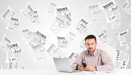 Business man at desk with stock market newspapers concept photo