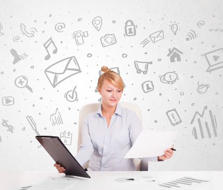 Business woman sitting at table with hand drawn media icons and symbols photo