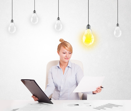 Business woman sitting at table with bright idea light bulbs photo