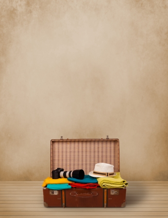 Retro tourist luggage with colorful clothes and copyspace on grungy background photo