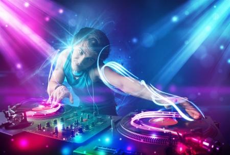 musica electronica: Joven mezcla de música Dj enérgico con poderosos efectos de luz Foto de archivo