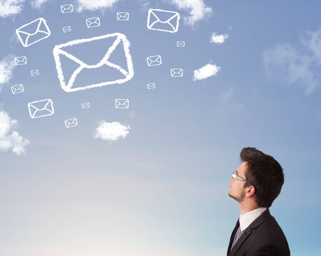 Businessman looking at mail symbol clouds on blue sky photo