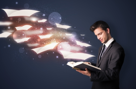 Young guy reading a book with flying sheets coming out of the book, magical reading concept photo