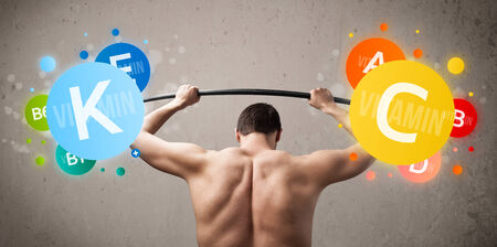 frail: Funny skinny guy lifting colorful vitamin weights