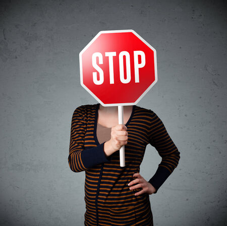 woman stop: Young lady standing and holding a stop sign in front of her head