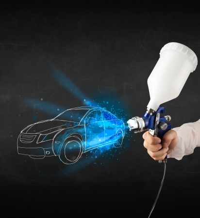Worker with airbrush gun painting hand drawn white car lines Stock Photo