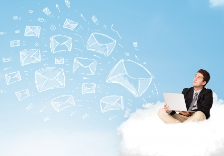 Young businessman sitting in cloud with laptop, sketched mails concept photo