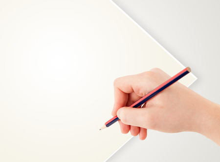 Human hand drawing with pencil on empty white paper template photo
