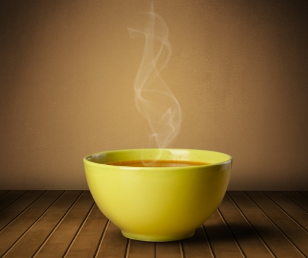 Fresh delicious home cooked soup with steam on wood deck photo