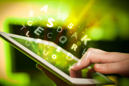 Hand touching tablet pc, letters concept photo