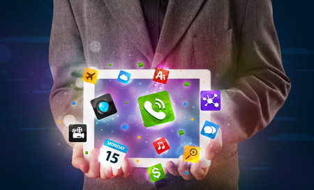 Young businessman holding a tablet with modern colorful apps and icons photo