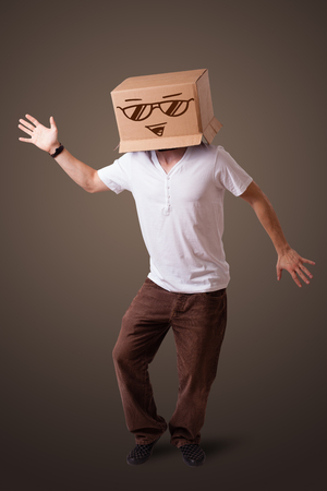 boxy: Young man standing and gesturing with a cardboard box on his head with smiley face