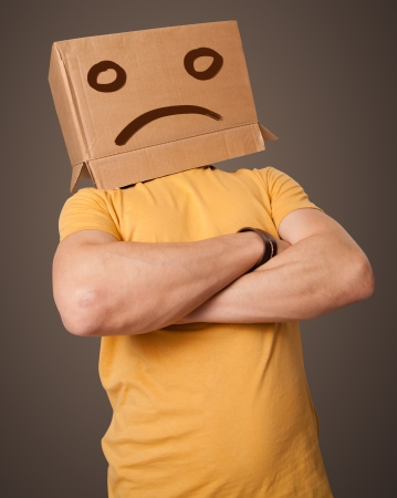 woeful: Young man standing with a brown cardboard box on his head with sad face Stock Photo