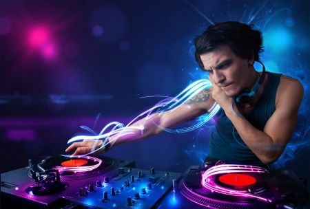dance and electronic: Young disc jockey playing music with electro light effects and lights